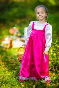 Dziewczynka w kostiumach maszy z kreskówki masza i niedźwiedź na jesienny las