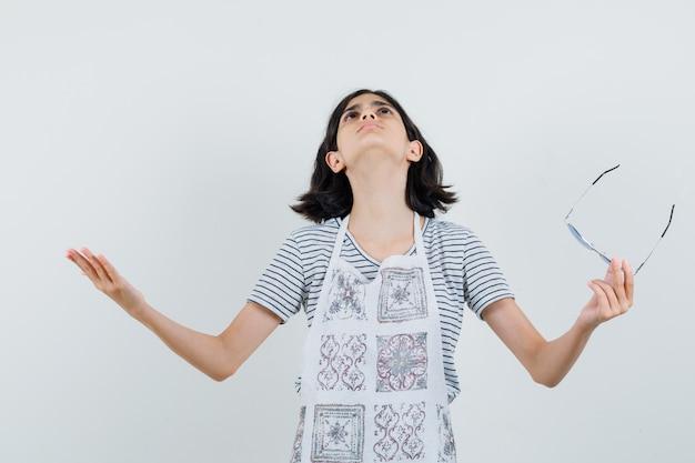 Dziewczynka w koszulce, fartuchu trzymająca okulary, unosząca ręce i wyglądająca na wdzięczną,