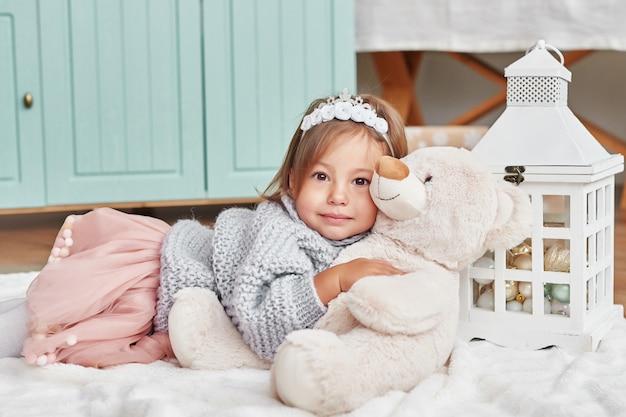 Dziewczynka w kuchni przy bożymi narodzeniami. dziecko patrzy i uśmiecha się.