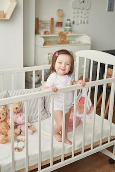 Dziewczynka w łóżeczku z zabawkami w pokoju dziecięcym
