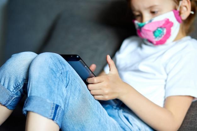 Dziewczynka w masce ochronnej za pomocą, grać na tablecie lub uczyć się podczas rozmowy wideo online