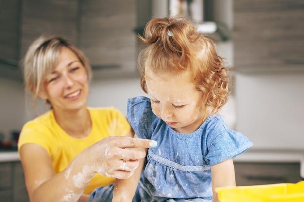 Dziewczynka w niebieskiej sukience pokrytej mąką patrzy na rękę matki