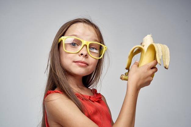 Dziewczynka w okularach z bananem w dłoniach jasnym tle