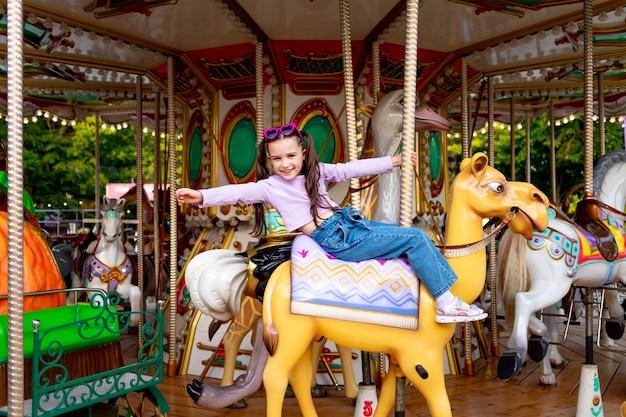 Dziewczynka w parku rozrywki jeździ na karuzeli i uśmiecha się ze szczęścia, koncepcja weekendów i wakacji szkolnych