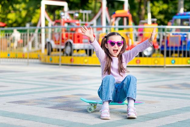 Dziewczynka w parku rozrywki latem jeździ na deskorolce i uśmiecha się ze szczęścia w pobliżu karuzeli w okularach przeciwsłonecznych, koncepcja wakacji letnich i wakacji szkolnych