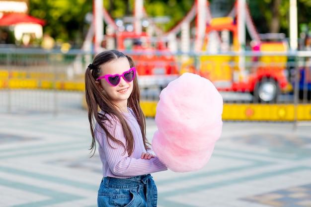 Dziewczynka w parku rozrywki latem zjada watę cukrową w pobliżu karuzeli w okularach przeciwsłonecznych, koncepcja wakacji letnich i wakacji szkolnych