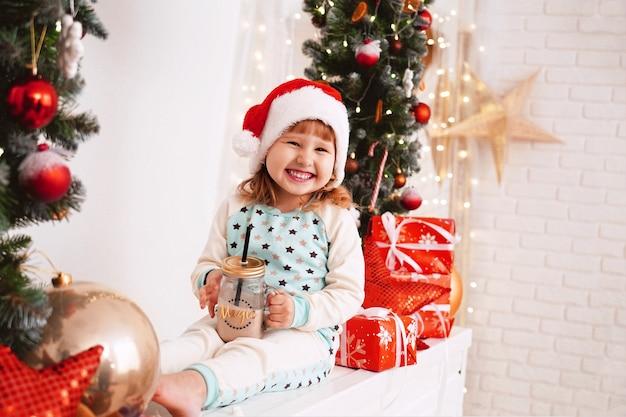 Dziewczynka w piżamie i czapce mikołaja pije mleko kakaowe