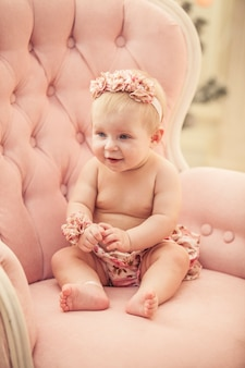 Dziewczynka w różowe ubrania i szczęśliwe wnętrze w stylu retro