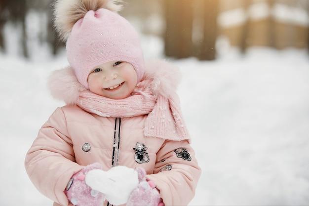 Dziewczynka w różowym kombinezonie w czapce z pomponem bawi się białą śnieżką. słoneczny zimowy dzień w parku miejskim, na świeżym powietrzu.