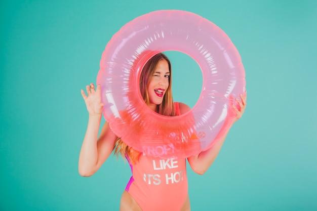 Dziewczynka w strój kąpielowy patrząc przez nadmuchiwany pierścień