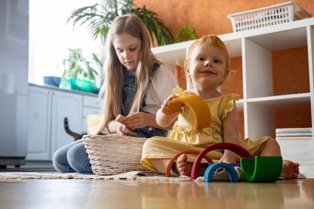 Dziewczynka w sukience układania tęczowego łuku konstrukcja blokowa budynek ekologiczna drewniana zabawka wieża