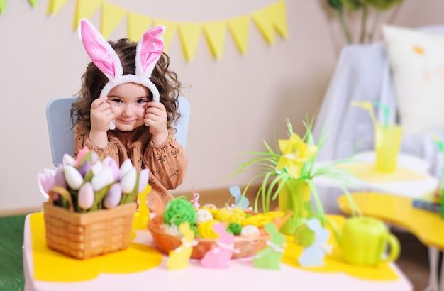 Dziewczynka w ucho królika siedzi przy stole na powierzchni wielkanocnego wystroju