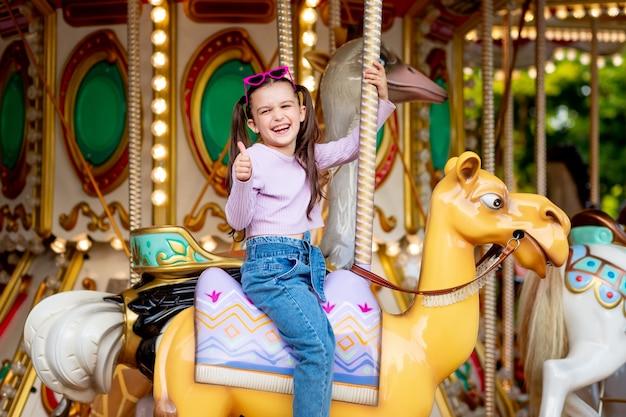 Dziewczynka W Wesołym Miasteczku Jeździ Na Karuzeli I Uśmiecha Się Ze Szczęścia Pokazując Klasę, Koncepcję Weekendów I Wakacji Szkolnych Premium Zdjęcia