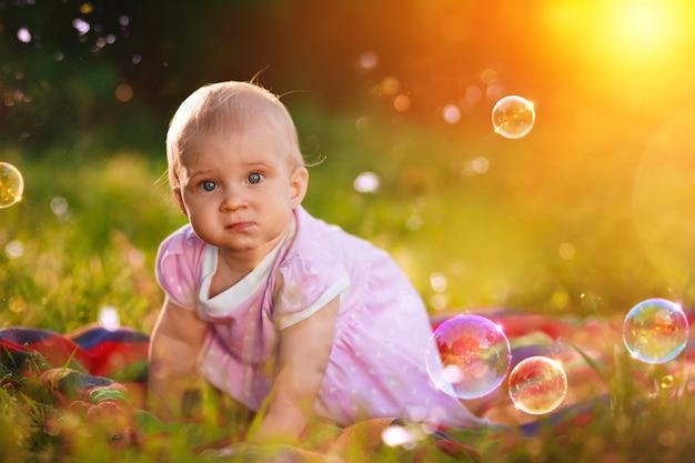 Dziewczynka w wieku 1 roku siedzi na zielonej trawie z bańkami mydlanymi w przyrodzie