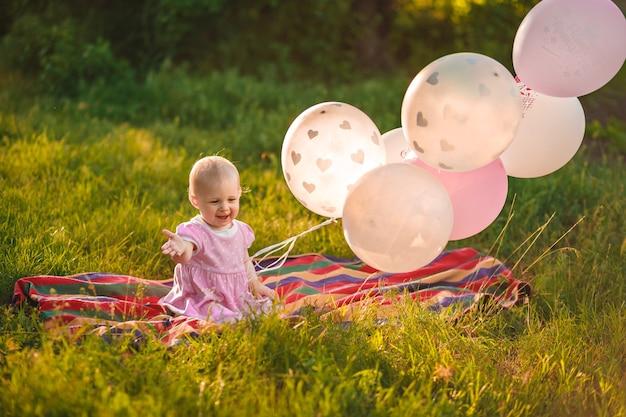 Dziewczynka w wieku 1 roku siedzi na zielonej trawie z różowymi i białymi balonami na łące na zewnątrz zbliżenie