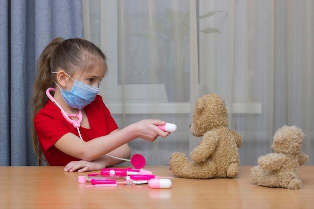 Dziewczynka w wieku przedszkolnym w masce medycznej bawiąca się zabawkami w szpitalu daje teddy'emu tablet