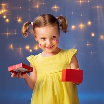 Dziewczynka w żółtej sukience i pudełku prezentowym w dłoniach odwraca wzrok i uśmiecha się na ścianie ze świecącymi światłami