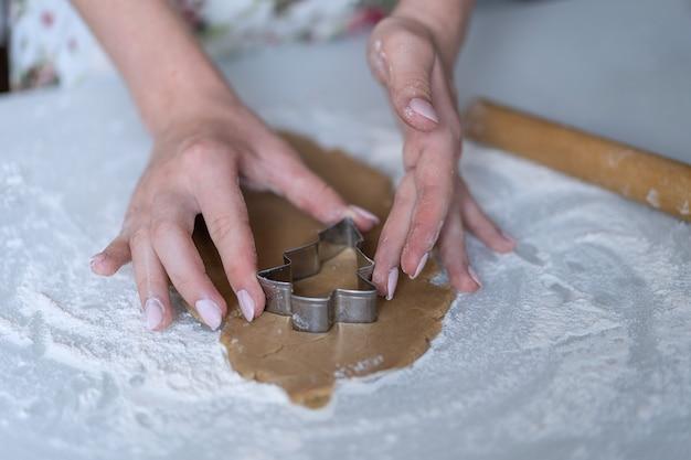 Dziewczynka wycina z ciasta świąteczne ciasteczka za pomocą form