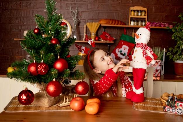 Dziewczynka z bałwanem w ciemnej kuchni w pobliżu choinki z czerwonymi kulkami raduje się i uśmiecha, koncepcja nowego roku i bożego narodzenia