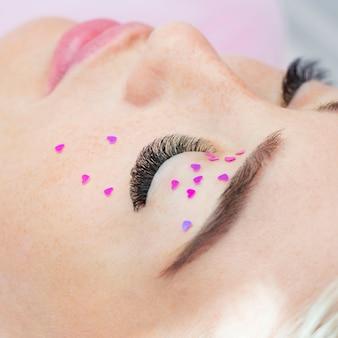 Dziewczynka z długimi przedłużonymi rzęsami, powiekami i twarzą ozdobiona różowymi serduszkami. ozdoba na oczy.