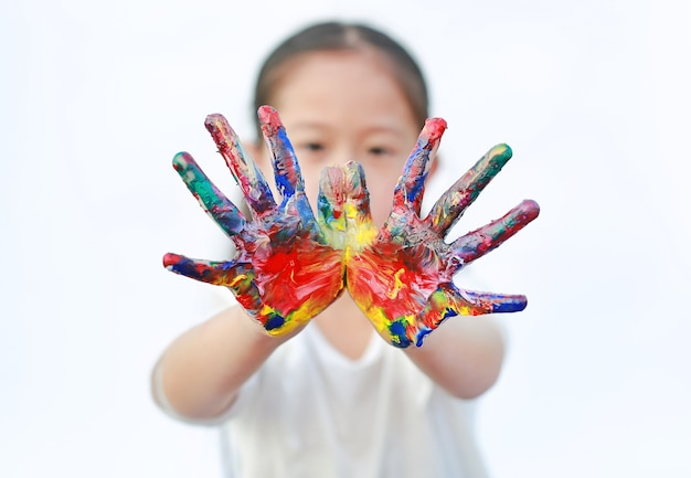 Dziewczynka z kolorowe ręce malowane na białym tle na białym tle. skoncentruj się na rękach dziecka.