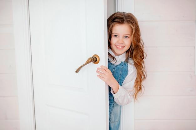 Dziewczynka z kręconymi włosami zagląda do drzwi i uśmiecha się
