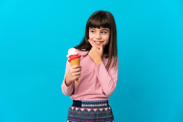 Dziewczynka z lodami cornet na białym tle na niebieskim tle, patrząc z boku i uśmiechnięty