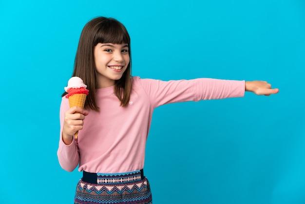 Dziewczynka z lodami cornet odizolowane na niebiesko, dając kciuki do góry gest