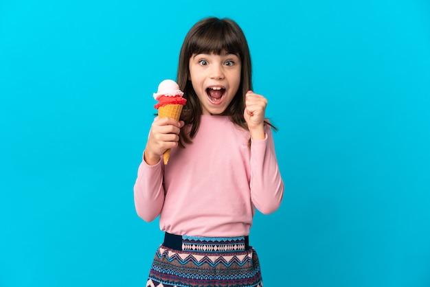 Dziewczynka z lodami kornetowymi na białym tle na niebieskim tle świętuje zwycięstwo w pozycji zwycięzcy