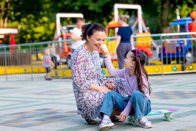 Dziewczynka z matką latem w wesołym miasteczku jedząca lody w pobliżu karuzeli, wygłupiająca się i śmiejąca się, koncepcja rodzinnych weekendów i wakacji szkolnych