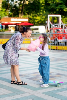 Dziewczynka z matką latem w wesołym miasteczku jedząca watę cukrową i lody w pobliżu karuzeli, wygłupiająca się i śmiejąca się, koncepcja rodzinnych weekendów i wakacji szkolnych