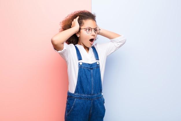 Dziewczynka z otwartymi ustami, wyglądająca na przerażoną i zszokowaną z powodu okropnego błędu, podnosząca ręce do płaskiej ściany