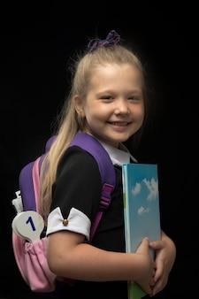 Dziewczynka z plecakiem szkolnym w dłoniach na czarnej ścianie. powrót do koncepcji szkoły i edukacji