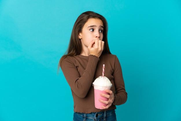 Dziewczynka z truskawkowym koktajlem mlecznym na białym tle na niebieskim tle, mając wątpliwości