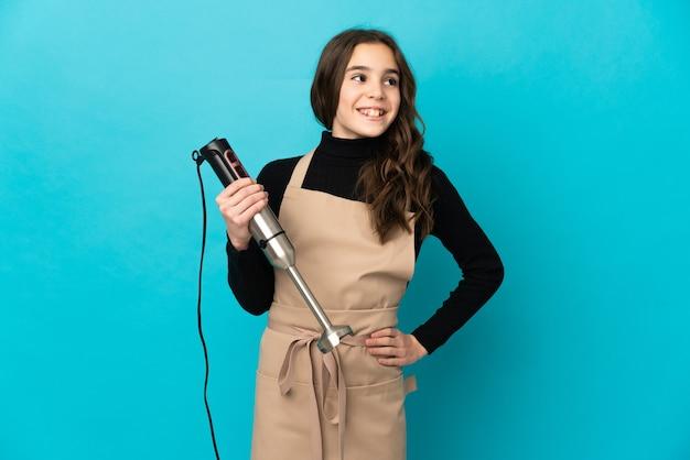 Dziewczynka za pomocą ręcznego miksera na białym tle na niebieskim tle pozowanie z rękami na biodrze i uśmiechnięty