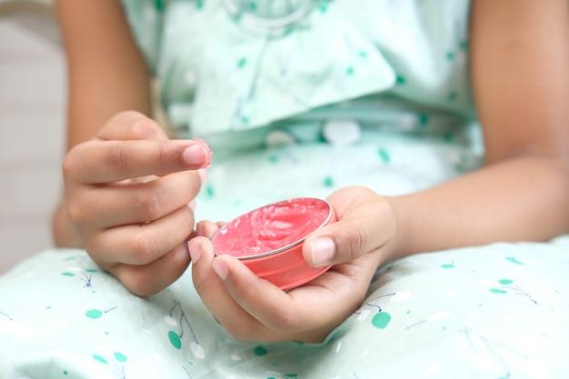Dziewczynka za pomocą wazeliny na skórę w domu z bliska