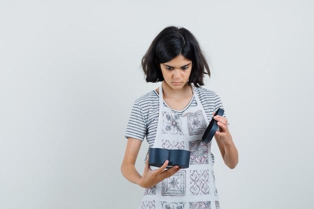 Dziewczynka zaglądająca do pudełka w koszulce, fartuchu i wyglądająca na zaskoczoną