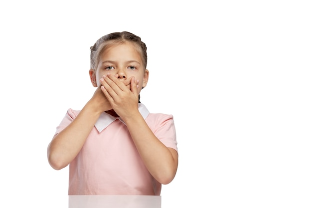 Dziewczynka zakryła usta dłońmi. pojedynczo na białym tle.