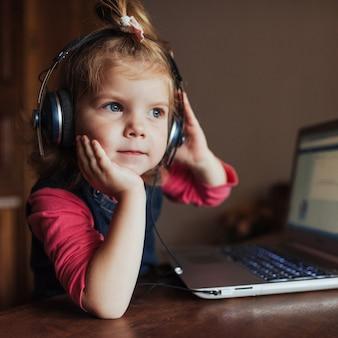 Dziewczynka ze słuchawkami, słuchanie muzyki, za pomocą laptopa