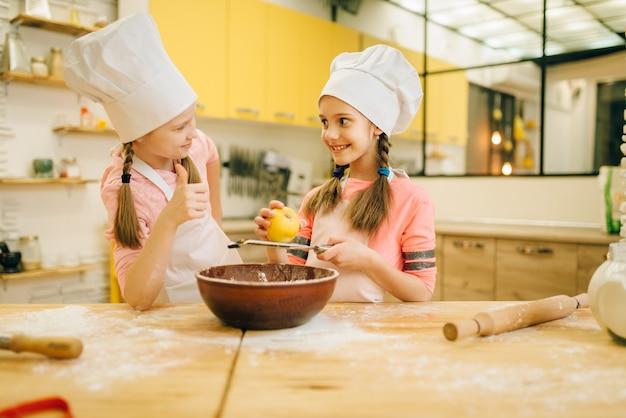 Dziewczynki gotują w czapkach wąchając proszek waniliowy