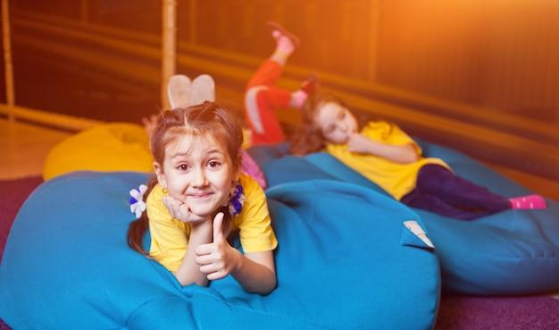 Dziewczynki leżą na torbie na krzesło i pokazują kciuki do góry w centrum dla dzieci