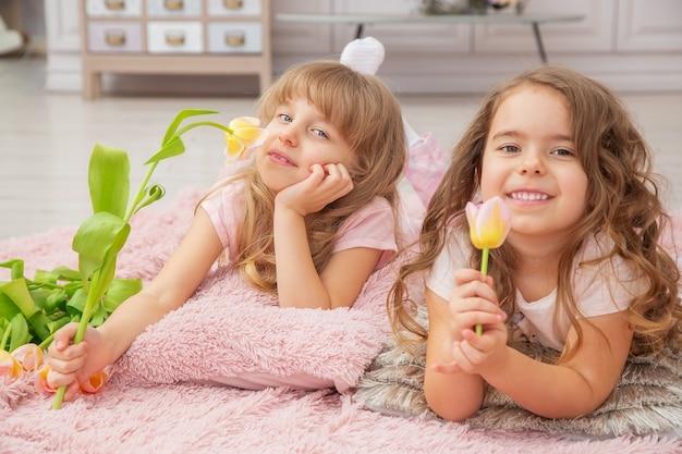 Dziewczynki o kaukaskim wyglądzie bawią się siedząc na podłodze w jasnym salonie w stylu skandynawskim z bukietem kwiatów