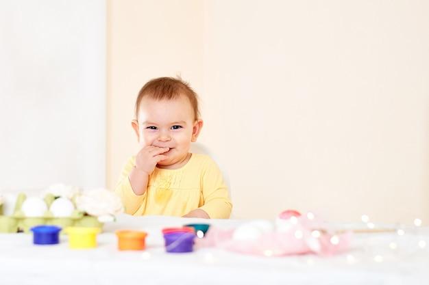 Dziewczynki obsiadanie przy stołem easter jajek obrazem i wakacje uśmiechnięty szczęśliwy dzieciństwo