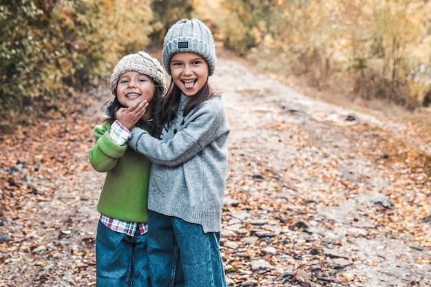 Dziewczynki uśmiechają się i cieszą życiem w jesienny dzień, przyjaźnią, siostrami, związkami, rodziną