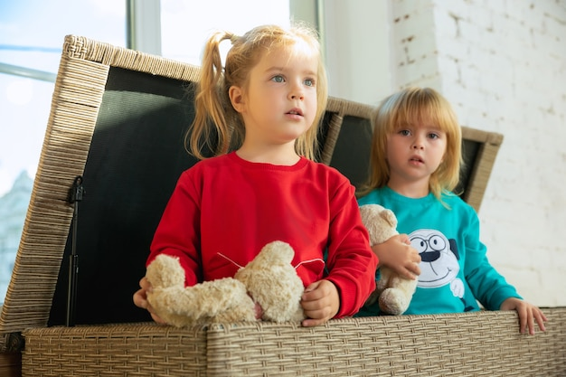 Dziewczynki w miękkiej ciepłej piżamie bawią się w domu. kaukaskie dzieci w kolorowych strojach, wspólna zabawa.