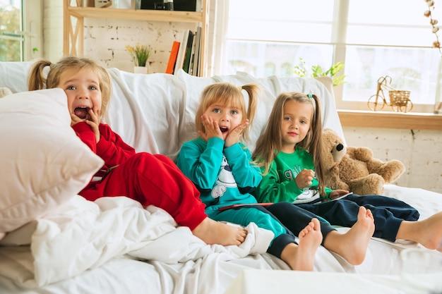 Dziewczynki w miękkiej ciepłej piżamie bawią się w domu