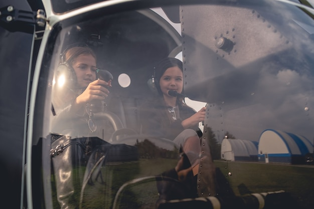 Dziewczynki w słuchawkach siedzące na fotelach pilota w helikopterze