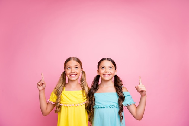 Dziewczynki z warkoczykami pozują na różowej ścianie