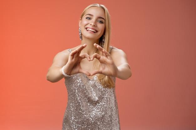Dziewczyno przyznaj się, że cię kocha. portret urocza delikatna kobieca młoda blond kobieta w srebrnej stylowej błyszczącej sukni wyciągnąć ramiona aparat pokazuje znak serca uśmiechając się szeroko, uwielbiam dziewczynę.