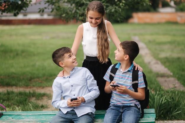 Dziewczyno zobacz, jak chłopak gra w gry online. dwóch chłopców gra w gry online w kwarantannie. młodzi chłopcy się uśmiechają i